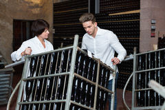 Male worker transporting wine bottles to storage. Glad cheerful positive male worker transporting wine bottles to storage at sparkling wine factory Stock Photo