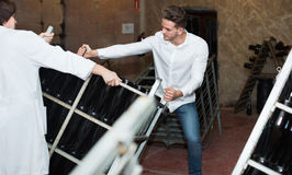 Male worker transporting wine bottles to storage. Positive male worker transporting wine bottles to storage at sparkling wine factory Stock Photos