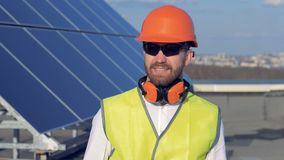 Male worker turns to camera and smiles, while standing on the roof near sun panels. 4K. Male worker turns to camera and smiles, while standing on the roof near stock video footage