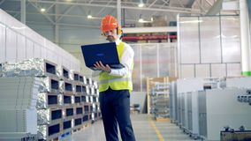 Male worker types on his laptop, standing at a warehouse, industrial plant. stock footage