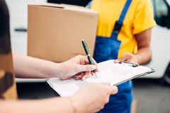 Male worker in uniform gives parcel to the client. Male worker in uniform gives a parcel to the client, distribution business. Cargo delivery. Empty container Royalty Free Stock Images
