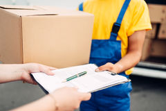 Male worker in uniform gives parcel to the client. Male worker in uniform gives a parcel to the client, distribution business. Cargo delivery. Empty container Stock Image