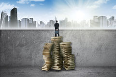 Male worker using books to see a city. Young entrepreneur standing on a pile of textbooks and look at a town Stock Image