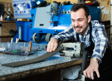 Male worker using his tools for repairing. Young diligent friendly smiling male worker using his tools for repairing in specialized workshop Royalty Free Stock Photography