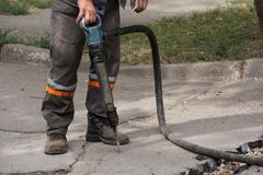 Male worker using jackhammer pneumatic drill machinery on road repair. Road repairing works with jackhammer. Male worker using jackhammer pneumatic drill Royalty Free Stock Image