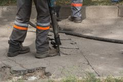 Male worker using jackhammer pneumatic drill machinery on road repair. Road repairing works with jackhammer. Male worker using jackhammer pneumatic drill Stock Image