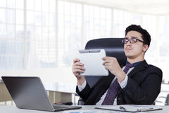 Male worker using tablet in office room. Successful young entrepreneur sitting on the office chair while using a digital tablet with laptop computer on the table Stock Photo