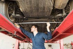 Male Worker Using Tape Measure To Check Wheel Alignment. Low angle view of male worker using tape measure to check wheel alignment in garage Royalty Free Stock Photos