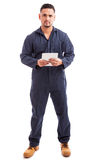 Male worker using technology. Full length view of a young man wearing overalls and using a tablet computer for work Royalty Free Stock Photography