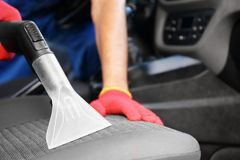 Male worker using vacuum cleaner. In car Stock Photo