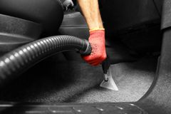 Male worker using vacuum cleaner. In car Stock Photos