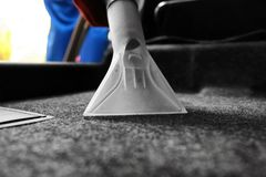 Male worker using vacuum cleaner. In car Royalty Free Stock Image