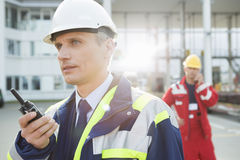 Male worker using walkie-talkie with colleague in background at shipping yard Stock Photos