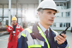 Male worker using walkie-talkie with colleague in background at shipping yard Stock Image