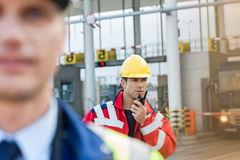 Male worker using walkie-talkie with colleague in foreground at shipyard Stock Image