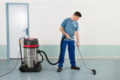 Male Worker With Vacuum Cleaner Stock Image