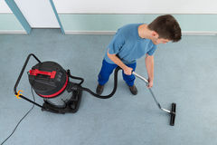 Male Worker With Vacuum Cleaner. Young Happy Male Worker Cleaning Floor With Vacuum Cleaner Royalty Free Stock Image