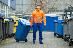 Male Worker Walking With Dustbin On Street. Happy Male Worker Walking With Dustbin On Street During Day Stock Images