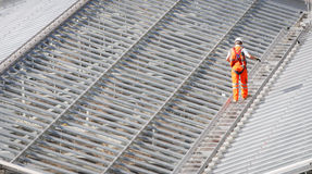 Male worker walking on a roof metal structure. Male Worker wearing an orange suit walking on the top of a steel roof structure of a railway station Royalty Free Stock Image