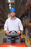 Male worker in warehouse. A male warehouse worker, driving a small forklift in the warehouse Royalty Free Stock Image