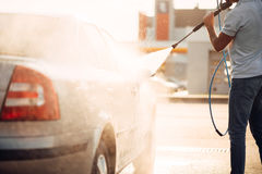 Male worker wash the car with high pressure washer. Car-wash station Royalty Free Stock Image