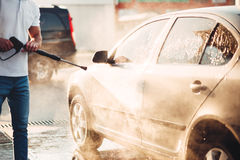 Male worker wash the car with high pressure washer. Car-wash station Royalty Free Stock Photography