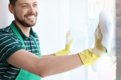 Male worker washing window glass. At home Royalty Free Stock Photo