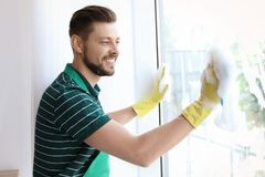 Male worker washing window glass. At home Stock Images
