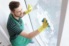 Male worker washing window glass. At home Stock Photo