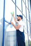 Male worker washing window glass. From outside Royalty Free Stock Images