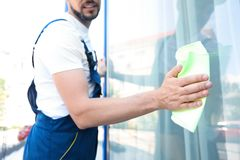 Male worker washing window from outside. Male worker washing window glass from outside Royalty Free Stock Photography