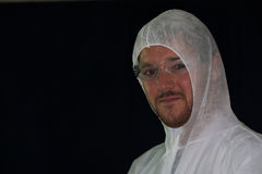 A male worker wearing a dust suit. A male worker wears a dust suit and safety glasses against a black background Stock Photos