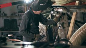 Male worker at a welding factory is examining metal construction to weld some piece of metal on it. Welding on an stock video