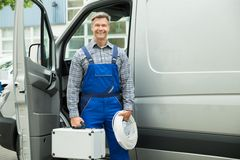 Male Worker With Wire And Toolbox. Happy Male Worker With Wire And Toolbox In Front Of Van Royalty Free Stock Image