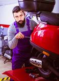 Male worker working at restoring motorbike in workshop. Male worker working at restoring motorbike in motorcycle workshop Stock Photography