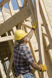 Male Worker Working At Site. Side view of a men holding a wood beam at construction site Royalty Free Stock Images