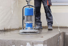 Male worker works with the diamond grinding machine, polishing the porch in front of the office building. the cement floor and co. Male worker works with the stock photos