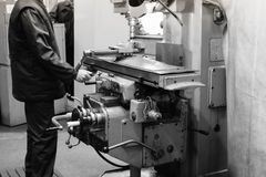 A male worker works on a larger metal iron locksmith lathe, equipment for repairs, metal work in a workshop at a metallurgical. Plant in a repair production stock images