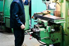 A male worker works on a larger metal iron locksmith lathe, equipment for repairs, metal work in a workshop at a metallurgical. Plant in a repair production royalty free stock images