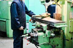 A male worker works on a larger metal iron locksmith lathe, equipment for repairs, metal work in a workshop at a metallurgical. Plant in a repair production royalty free stock photography