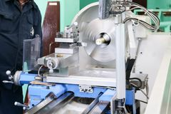 A male worker works on a larger metal iron locksmith lathe, equipment for repairs, metal work in a workshop at a metallurgical. Plant in a repair production stock photo