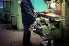 A male worker works on a larger metal iron locksmith lathe, equipment for repairs, metal work in a workshop at a metallurgical. Plant in a repair production stock photos