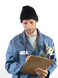 Male Worker Writing Notes. A male blue collar worker takes notes on a clipboard. Isolated on a white background Stock Photo
