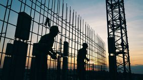 Male workers build a house on a sunset background. 4K stock video footage