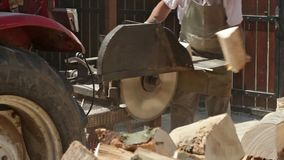 Male workers cutting firewood logs with circular saw - sliding camera stock footage