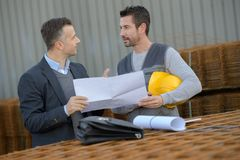 Male workers discussing outside industry. Factory Royalty Free Stock Images