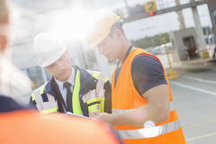 Male workers discussing over clipboard in shipping yard Royalty Free Stock Photography