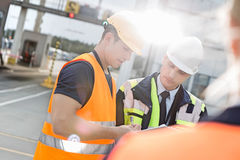 Male workers discussing over clipboard in shipping yard Stock Photography