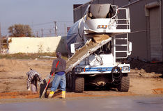 Male Workers Pouring Cement. Two male construction workers are in the process of pouring concrete from a large mixing truck.  Job-site is an industrial area with Stock Images