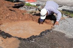 Male workers repair pipe water main broken. Tube underground water on road Stock Photos